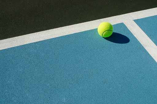 Tennis ball rests on blue tennis court 1050929002