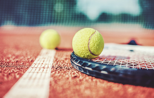 Tennis ball with racket on the tennis court. Sport, recreation concept 1093339590