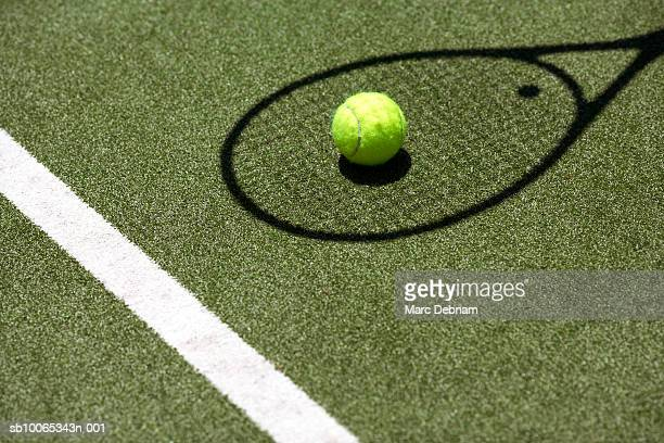 Tennis ball with racket shadow on court