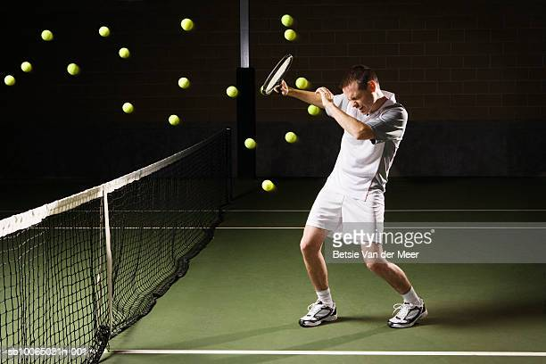 Tennis balls hitting tennis player