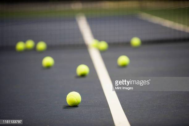 tennis balls on a tennis court - tennis ball stock pictures, royalty-free photos & images