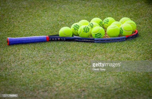 Tennis balls sit atop a racquet on a practice court during the Wimbledon Lawn Tennis Championships at the All England Lawn Tennis and Croquet Club at...