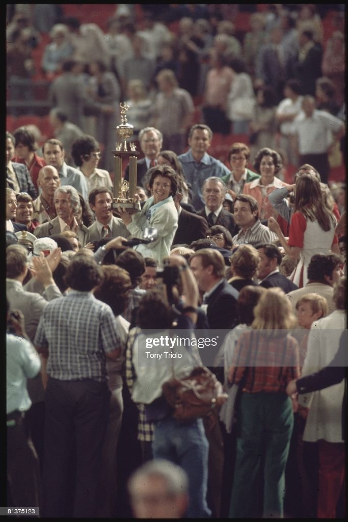 Battle of Sexes, Billie Jean King victorious with trophy and surrounded by fans and media after winning match vs Bobby Riggs at Astrodome, Houston, TX 9/20/1973
