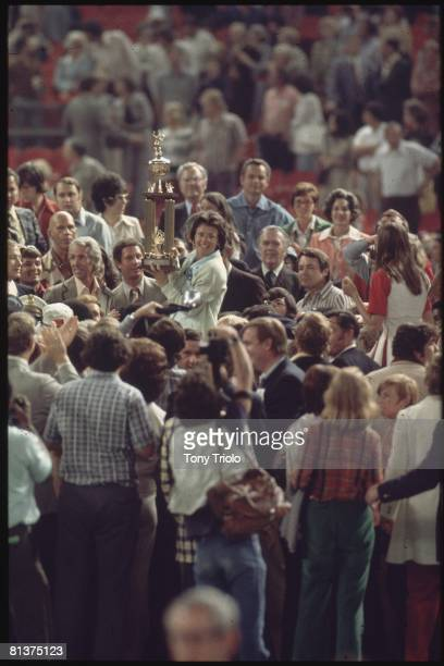 Tennis Battle of Sexes Billie Jean King victorious with trophy and surrounded by fans and media after winning match vs Bobby Riggs at Astrodome...