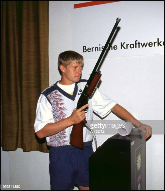 """Tennis Champ Yevgeny Kafelnikov, Russia was photographed holding an electronic """"Hit the Dancing Bear"""" shot gun in the Player Lounge at the 1994..."""