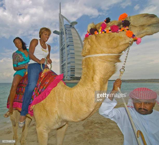 Tennis champions Serena and her sister Venus Williams ride a camel on the beach in front of the Burj Al Arab hotel during the WTA Dubai Women's Duty...