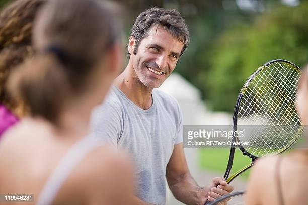 Tennis coach demonstrating for students
