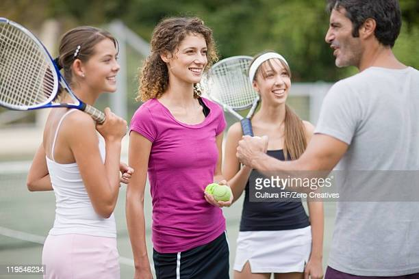 Tennis coach talking to students