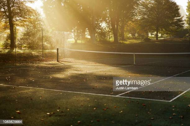 tennis court in autumn with sun beams and mist - tennis stock-fotos und bilder