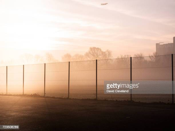 Tennis court wire fence and overhead airplane in misty park at sunrise