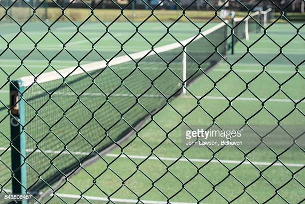 Tennis courts surrounded by wire mesh fence