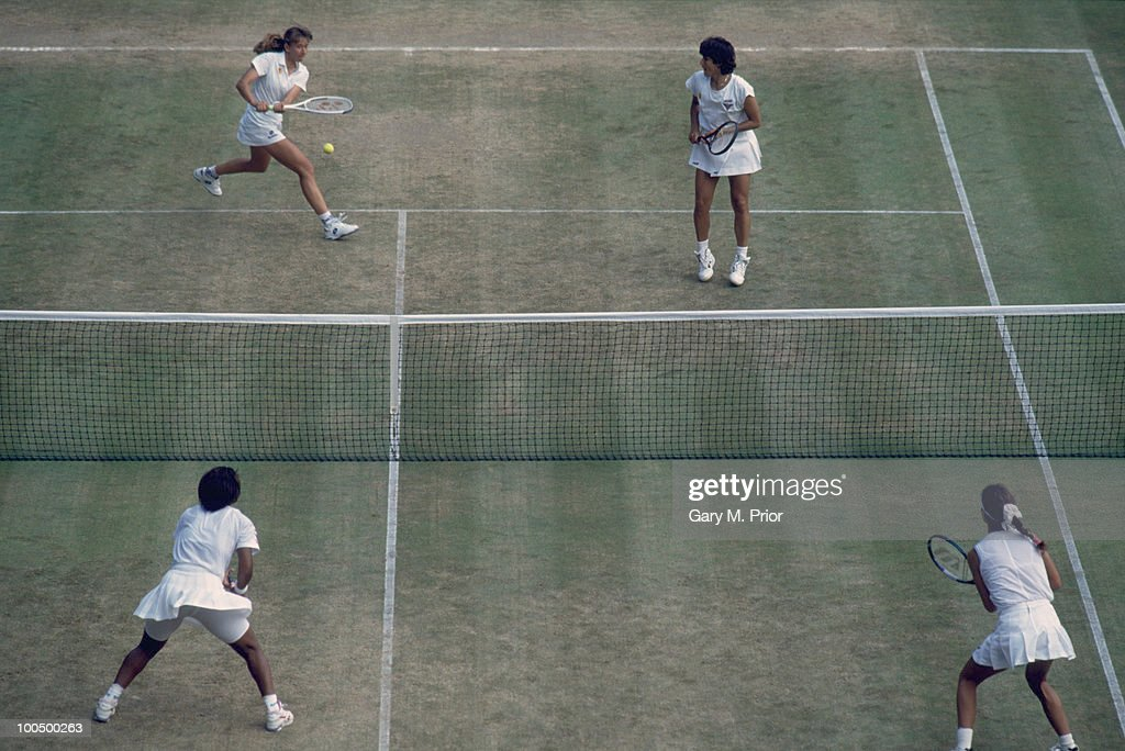 Tennis doubles partners Natasha Zvereva (top left) and Gigi Fernandez (top right) in play against Zina Garrison and Mary Joe Fernandez in the Women's Doubles at Wimbledon, 1993. Fernandez and Zvereva went on to win the Women's Doubles tournament.