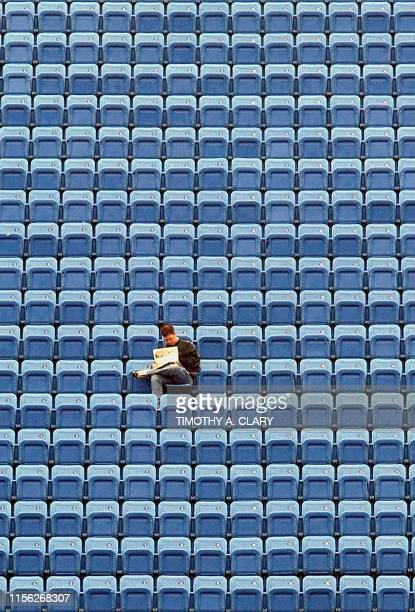 A tennis fan braves the rain and reads his paper 02 September at the Arthur Ashe Stadium as rain delays matches for the second straight day at the...
