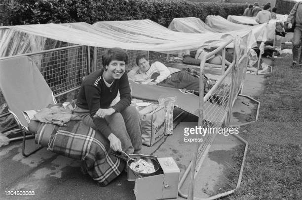 A tennis fan cooking bacon on a portable stove while camping out in the queue outside the gates of the All England Lawn Tennis and Croquet Club...