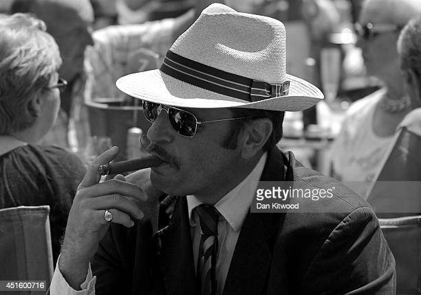Tennis fan is seen smoking a cigar on day nine of the Wimbledon Lawn Tennis Championships at the All England Lawn Tennis and Croquet Club at...