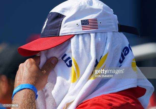 A tennis fan keeps cool under a towel while watching Ekaterina Makarova of Russia and Julia Goerges of Germany during their 2018 US Open women's...