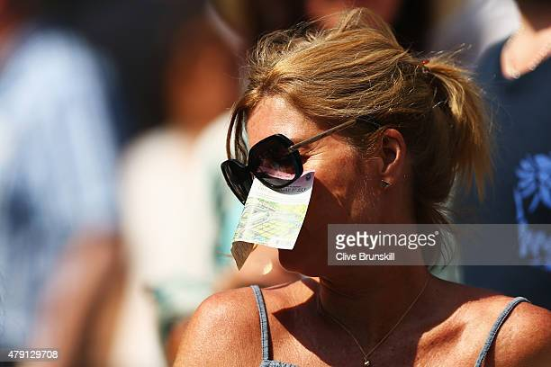 Tennis fan uses her ticket to shelter her nose from the sun during the Gentlemens Singles Second Round match between Marin Cilic of Croatia and...