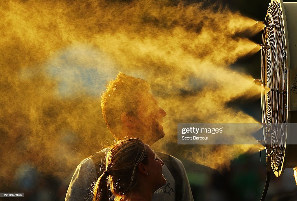 Tennis fans cool off from the heat in front of mist cooling fans on day one of the 2017 Australian Open at Melbourne Park on January 16, 2017 in Melbourne, Australia.