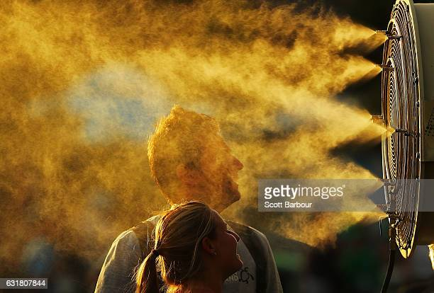 Tennis fans cool off from the heat in front of mist cooling fans on day one of the 2017 Australian Open at Melbourne Park on January 16 2017 in...