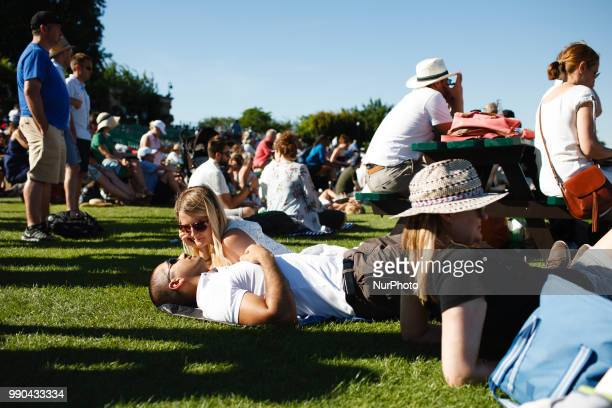 Tennis fans relax outside Centre Court in the fan viewing area popularly known as 'Henman Hill' on the opening day of the 2018 Wimbledon...