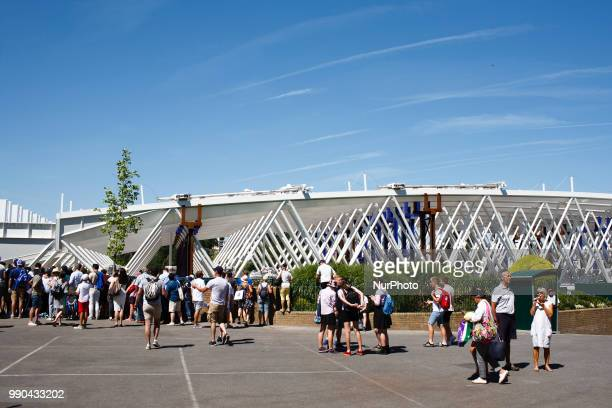 Tennis fans stand near the tobeinstalled retractable roof for No 1 Court on the opening day of the 2018 Wimbledon Championships at the All England...