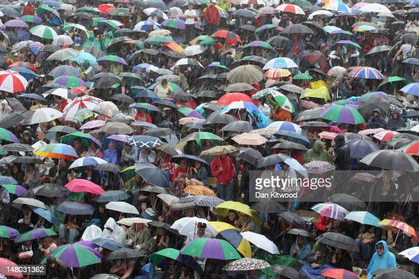 Tennis fans stay in their spots during a torrential rain storm during the third set on 'Murray Mount' on the final day at Wimbledon on July 8 2012 in...