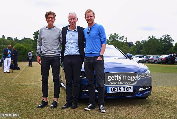Tennis fans Tom Payne and Nick Webb pose for a picture with 3-time Wimbledon Champion John McEnroe in front of the Jaguar XE as part of the...