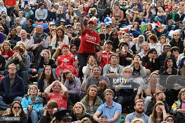 Tennis fans watch Roger Federer take match point during the final game on 'Murray Mount' on the final day at Wimbledon on July 8 2012 in London...