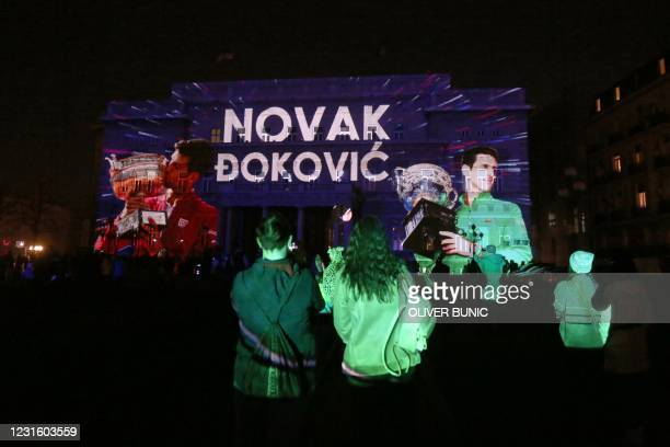 Tennis fans watch videos of most important moments of the career of Serbian tennis player Novak Djokovic projected on Belgrade's city hall to...