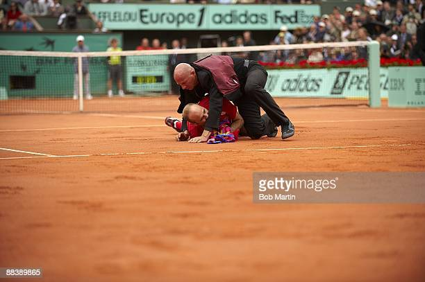 French Open View of spectator Jimmy Jump getting tackled by security officers after running onto court during Roger Federer vs Robin Soderling Men's...