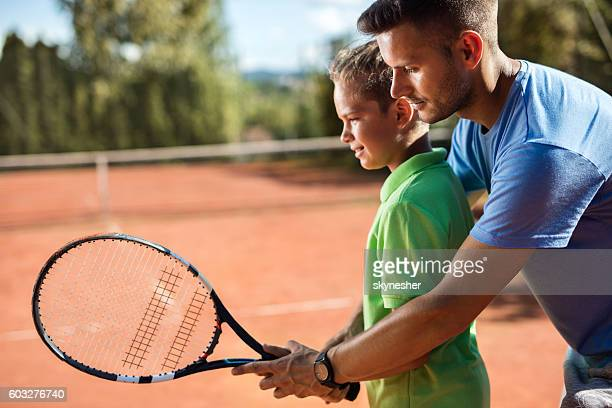 Tennis instructor assisting little boy on the tennis court.