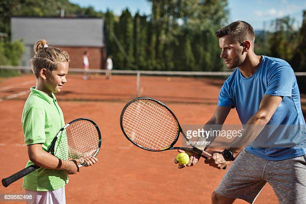 Tennis instructor teaching small boy during training class.