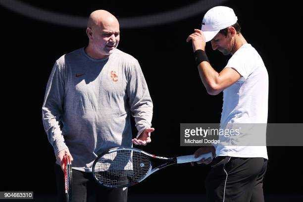 Tennis legend Andre Agassi gives some tips to Novak Djokovic of Serbia during a practice session ahead of the 2018 Australian Open at Melbourne Park...