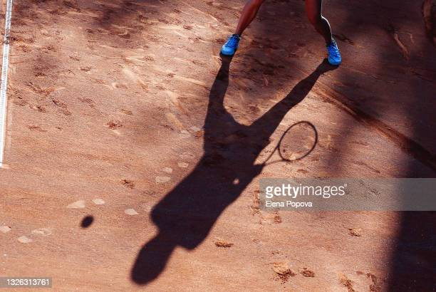 tennis moment, low section and large shadow of woman playing at the  clay tennis court - tennis tournament stock pictures, royalty-free photos & images
