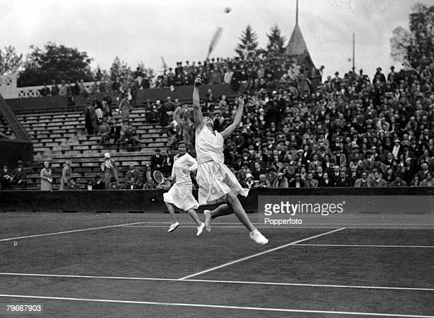 Tennis Paris France 29th May Helen Wills Moody reaches for the ball watched by partner Elizabeth Ryan as she returns the ball to Mrs Fearnley...