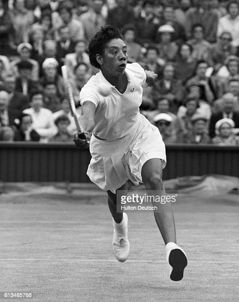 Tennis player Althea Gibson hits the ball during a match at the 1956 Wimbledon Championships