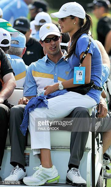 Tennis player Ana Ivanovic of Serbia sits on partner Adam Scott of Australia's knee at the conclusion of the President's Cup tournament in Melbourne...