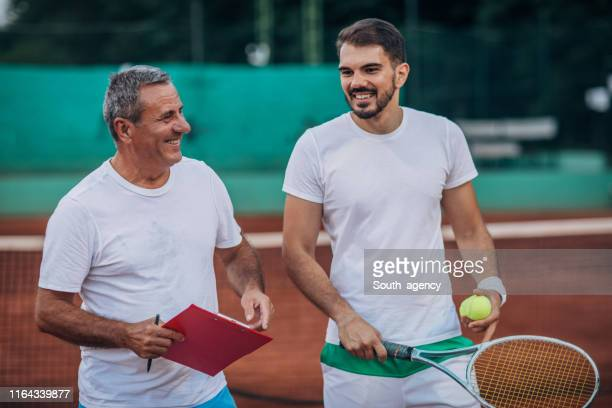 tennis player and mature tennis coach on clay court - tennis player stock pictures, royalty-free photos & images