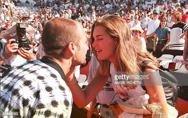US tennis player Andre Agassi gets a kiss from his girlfriend US actress Brooke Shields after winning over compatriot Pete Sampras in the finals of...