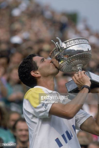 Tennis player Andres Gomez kisses the trophy he has just received after winning the French Open against Andre Agassi