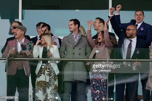 Tennis player Andy Murray watches the racing as his wife Kim raises her arms aloft as the runners near the finish at Cheltenham Racecourse on March...