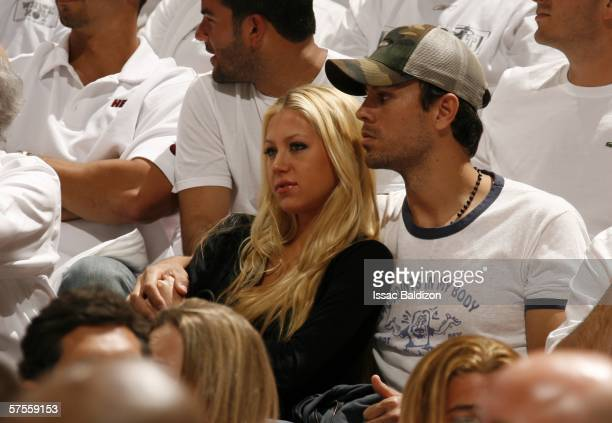 Tennis player Anna Kournikova and singer Enrique Iglesias watch the New Jersey Nets play against the Miami Heat in game one of the Eastern Conference...