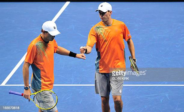 US tennis player Bob Bryan and his partner Mike Bryan touch fists during their group A doubles match against Spain's Marc Lopez and Spain's Marcel...