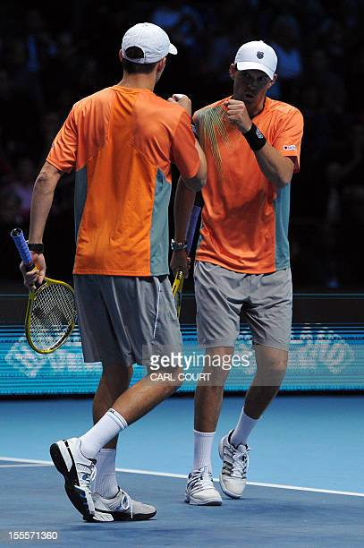 US tennis player Bob Bryan and his partner US player Mike Bryan touch fists during their loss to Spain's Marc Lopez and Spain's Marcel Granollers in...
