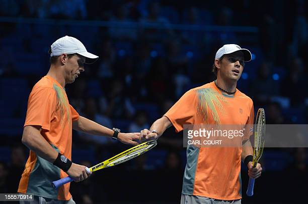 US tennis player Bob Bryan and his US partner Mike Bryan touch hands between points against Spain's Marc Lopez and Spain's Marcel Granollers during...