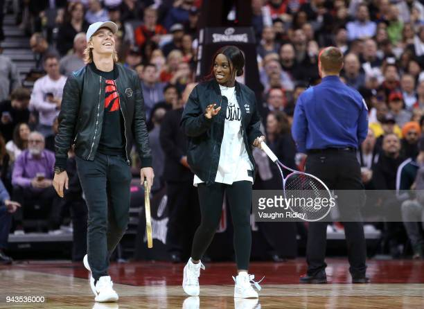 Tennis player Denis Shapovalov and WTA Tennis player Sloane Stephens play tennis on court during a break in play during the first half of an NBA game...