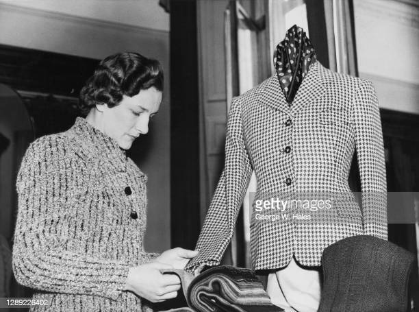 Tennis player Helen Jacobs of the United States examines the cloth and texture of a jacket during a visit to a London sportswear company on 11th...
