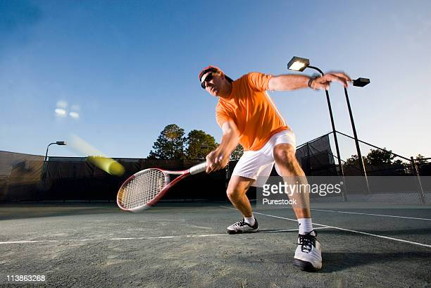 Tennis player hitting a volley at the service line