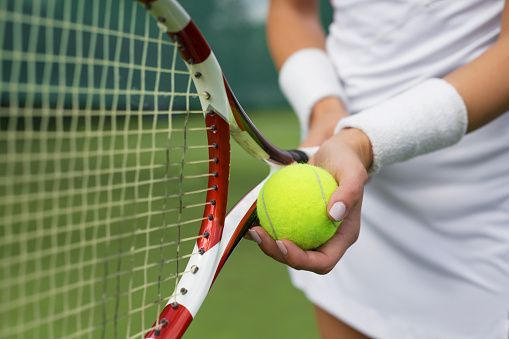 Tennis player holding racket and ball in hands 503392332