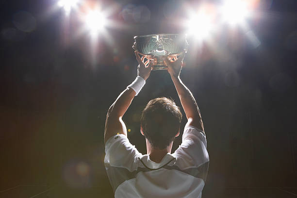 Tennis player holding winner's cup, rear view